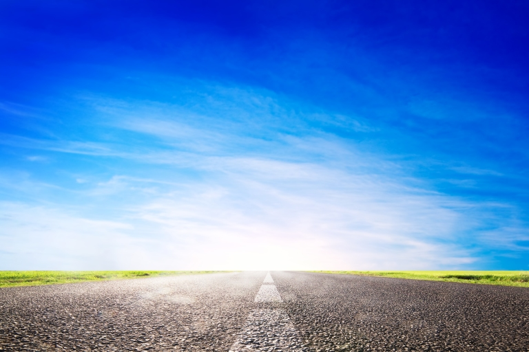 Long empty asphalt road, highway towards sun